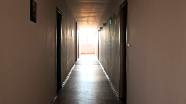 Dark corridor with cabinet doors and window