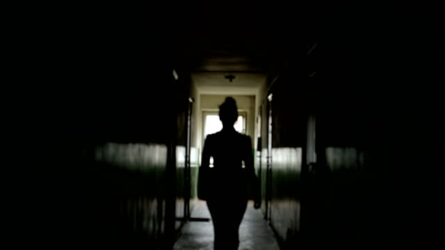 Dark exposure silhouette of a woman view from the back in defocus. A female figure is walking along a dark corridor, moving away from the camera. Dark exposure silhouette of a woman view from the back. A female figure is walking along a dark corridor, moving away from the camera. The mood of the horror of melancholy and hopelessness. 4k low key low lighting stock videos & royalty-free footage