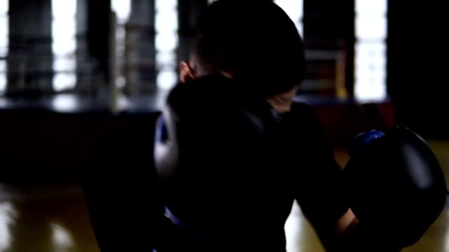 Dark haired man aggressively hitting the boxing bag, hard kicks. Motivation in sport. Old style gym, daytime. Close up