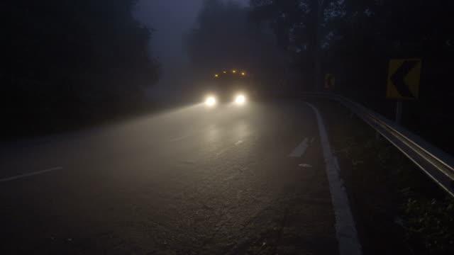 stockvideo's en b-roll-footage met 4k ws, donkere mistige kromme weg met vrachtwagen op de vroege ochtend. - mist donker auto