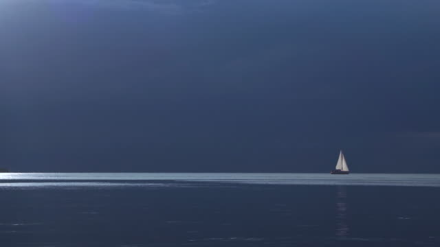 Dark moody sky over a sailboat in calm waters video