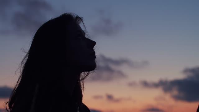 profilo scuro della donna dai capelli lunghi che guarda verso il cielo godendosi la sera d'estate - hippy video stock e b–roll