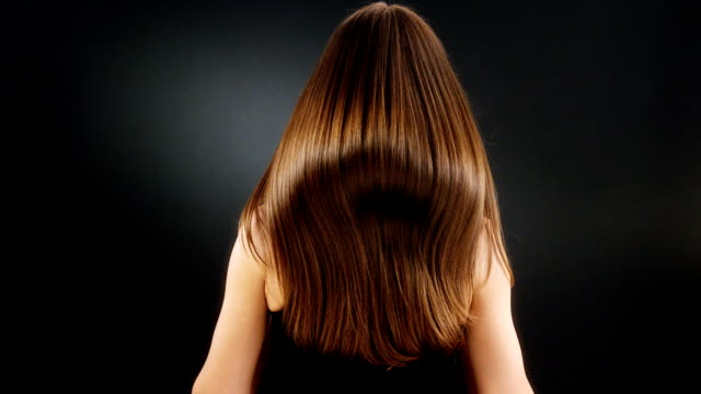 Dark shiny hair View from behind of girl with shining dark hair. Studio shoot. long hair stock videos & royalty-free footage