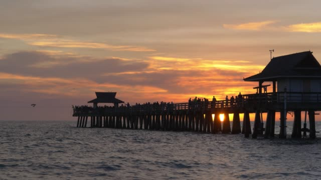 Dark silhouette of a pier over the ocean at sunset