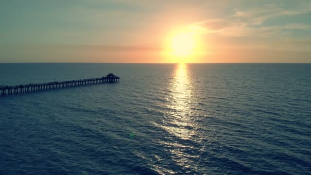 Dark silhouette of a pier over the water at sunset video