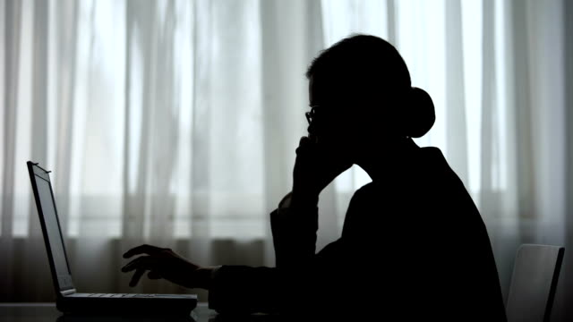 dark silhouette of businesswoman talking on phone at night making note on laptop - shifts call centre video stock e b–roll