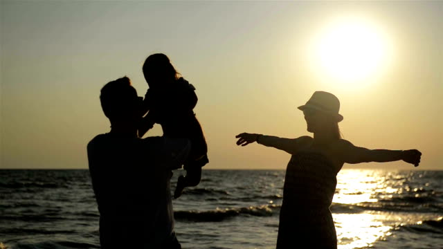 Dark Silhouettes of Mother in Summer Hat and Father with Little Daughter near the Sea During Sunset. Strong Man Swirls Girl above His Head video