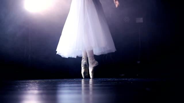 A dark stage behind white dancing ballerinas legs. video