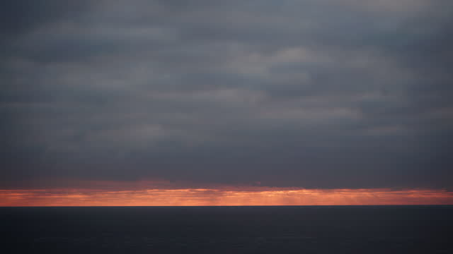 Dark stormy clouds moving over sea at sunrise, time lapse