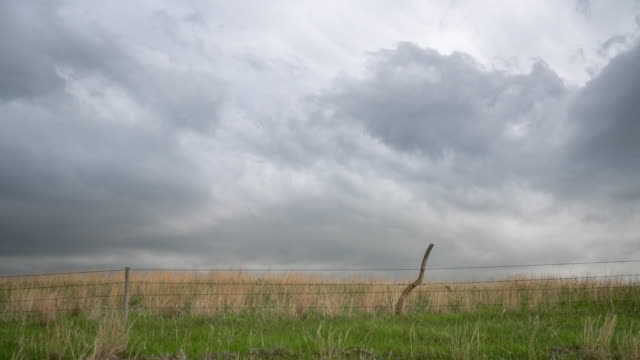 Dark stormy clouds over prairie with a barbed wire cattle fence