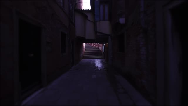 Dark street of Venice with subway Poorly lit path of the city of Venice with houses on the sides and a bridge ahead low lighting stock videos & royalty-free footage