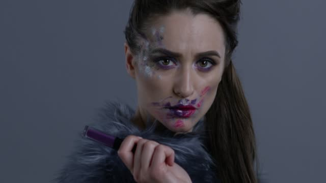 dark-haired fashion model in silver fox fur holds violet lipstick. fashion video. - organizm żywy filmów i materiałów b-roll