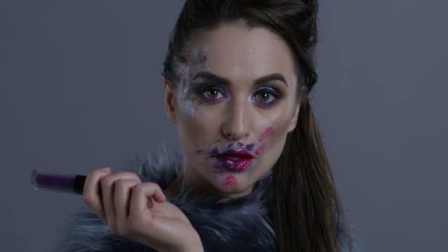 dark-haired fashion model in silver fox fur holds violet lipstick. fashion video. - clavicola video stock e b–roll
