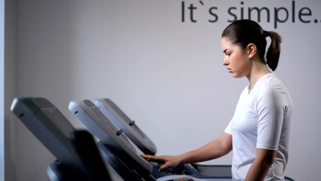 dark-haired girl is engaged in walking on the treadmill in the gym. 4k slow mo - runner rehab gym video stock e b–roll