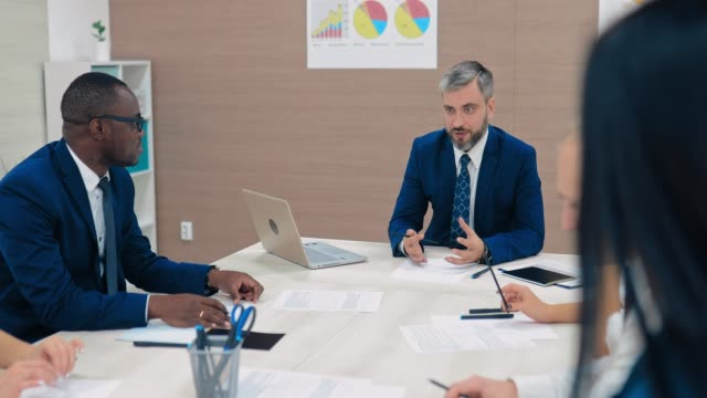 stockvideo's en b-roll-footage met donker gevild zakenman in een briefing in een modern business center. vergadering van financiële directeuren, planning. - bedrijfsstrategie