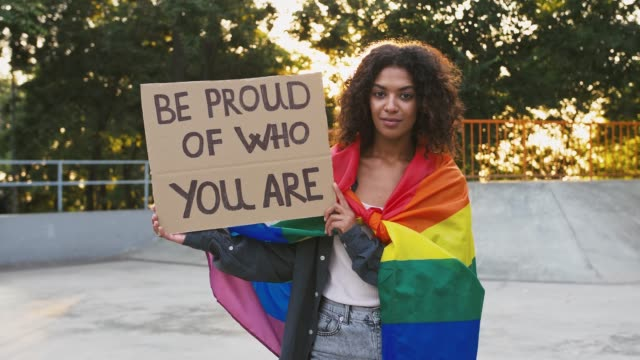 Dark-skinned woman in colorful LGBT pride flag. Showing cardboard poster, inscription be proud of who you are. Posing at sunny skatepark. Close up Young dark-skinned woman wrapped in colorful LGBT pride flag. She smiling and showing cardboard poster with inscription be proud of who you are, posing at sunny skatepark. Pride day. Close up pride stock videos & royalty-free footage