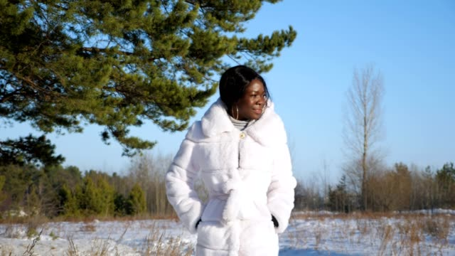 dark-skinned woman in fur coat walks on snowy forest glade