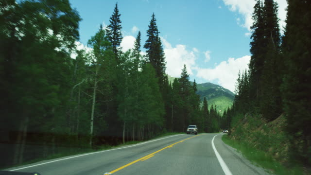 Dashboard Shot of Vehicles Driving along a Forest-Lined Section of Red Mountain Pass (Million Dollar Highway/US 550) in the San Juan Mountains/Rocky Mountains in Summer on a Partly Cloudy Day