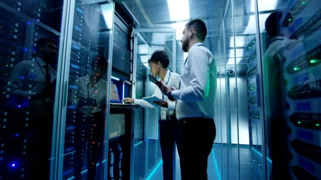 data center colleagues with tablets - supporto tecnico video stock e b–roll