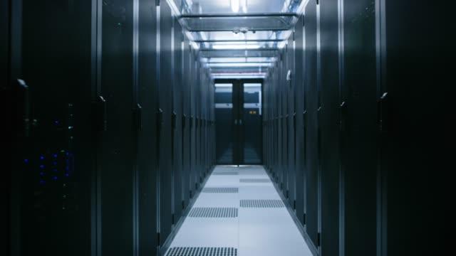 data center med mellan två rader med fullt fungerande serverrack. modern telekommunikation, cloud computing, artificiell intelligens, databas, superdator teknik koncept. rör sig genom kameran skott - server room bildbanksvideor och videomaterial från bakom kulisserna