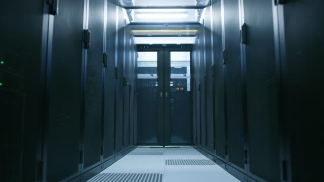 完全に運用サーバーの 2 つの行の間のデータ ・ センターのラックします。通信、クラウド ・ コンピューティング、人工知能、データベース、スーパー コンピュータ技術の概念。バックウ� - スーパーコンピューター点の映像素材/bロール