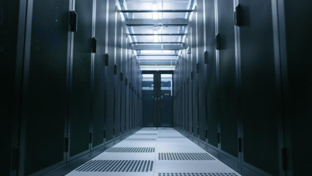 data center med mellan två rader med fullt fungerande serverrack. begreppet telekommunikationer, cloud computing, artificiell intelligens, databas, superdator teknik. rör sig genom skott - server room bildbanksvideor och videomaterial från bakom kulisserna