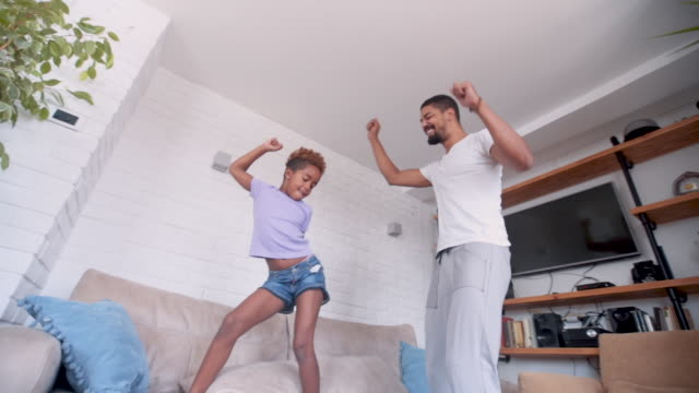 daughter and dad dancing and jumping - kitchen room video stock e b–roll