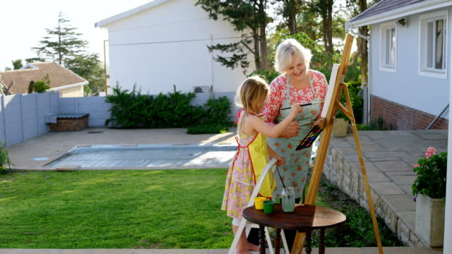 daughter and grandmother painting on canvas 4k - 60 69 anni video stock e b–roll