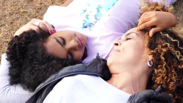 stockvideo's en b-roll-footage met dochter en moeder liggen genieten van de dag in het park - activiteit
