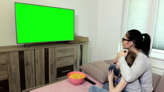 vídeos de stock e filmes b-roll de daughter and mother watching tv with green screen - tv e familia e ecrã