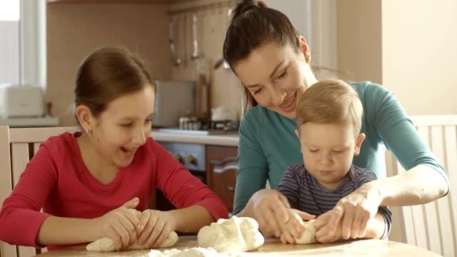 Tochter und Sohn helfende Mutter kochen, Kneten von Teig in der Küche und Familie Zeit miteinander zu verbringen – Video