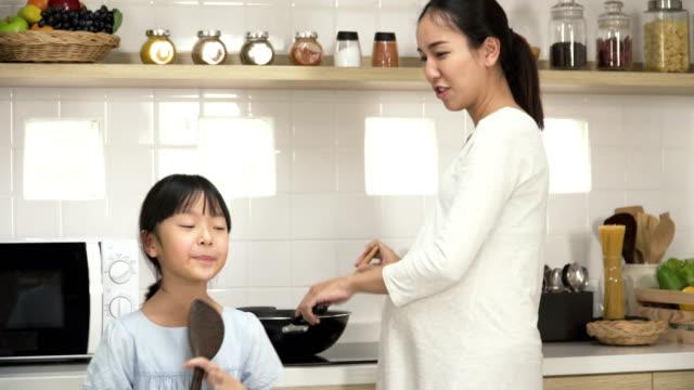 妊娠中の母親が台所で料理をしながら歌を歌って踊ったりの娘 - 母娘 笑顔 日本人点の映像素材/bロール