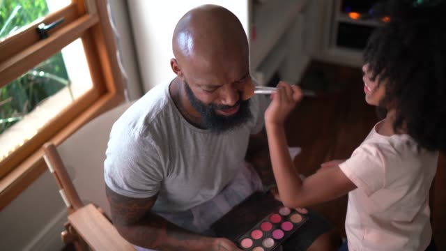 Daughter doing makeup to shy father at home