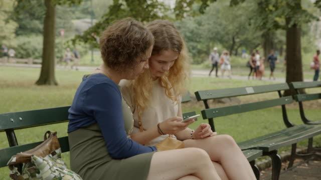 娘女の子ニューヨーク母女ベンチ スマート フォン ソーシャル メディア - ベンチ点の映像素材/bロール