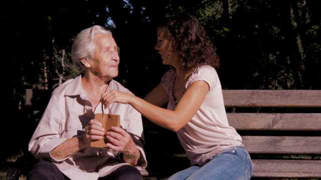 daughter gives an elderly mother a gift. - mothers day stock videos & royalty-free footage
