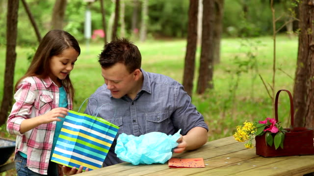 Daughter gives daddy Father's Day gift. Outdoors. Child, parent.ld, parent. video