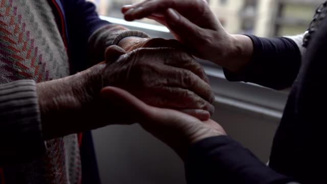 dotter som ger sin kärlek och omsorg till sin gamla far hemma, kvinna vårda och trösta sina gamla skrynkliga händer, senior man i pension behöver hjälp. äldre man, gamlemans händer - krama bildbanksvideor och videomaterial från bakom kulisserna
