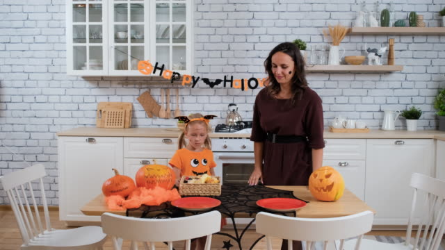 Daughter Helping Mother to Prepare for Halloween