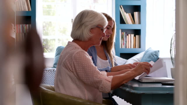 Daughter Helping Senior Mother With Paperwork In Home Office Adult daughter helping mother to fill in form before she adds her signature. Shot in 4k on Sony FS700 at frame rate of 25fps form filling stock videos & royalty-free footage