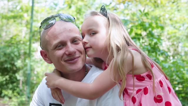Daughter hugs dad for walk in the forest. Positive communication within family.