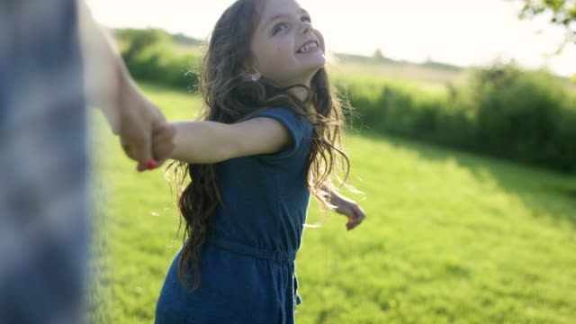 Daughter Leading Her Mother A mother and daughter are enjoying themselves outdoors. The daughter is holding the mothers hand, leading her through the grass. love emotion stock videos & royalty-free footage
