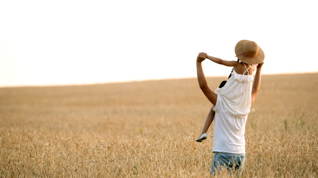a daughter, like her father, rotates her on her shoulders in a wheat field. slow motion - giuntura umana video stock e b–roll