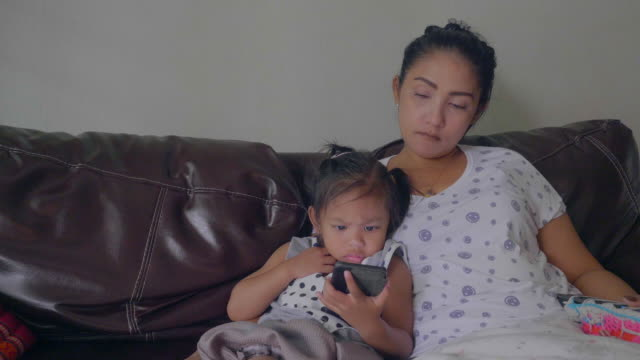 Daughter lying on the phone with her mother at home stock video