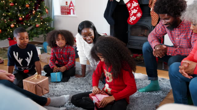 Daughter Opening Gift As Multi Generation Family Celebrate Christmas At Home Together