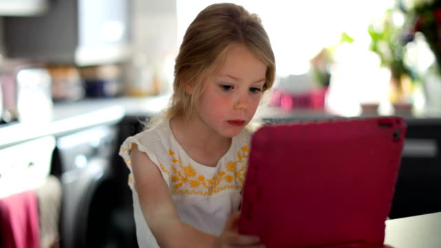 daughter playing on the digital tablet while mother does washing up - pesche bambino video stock e b–roll