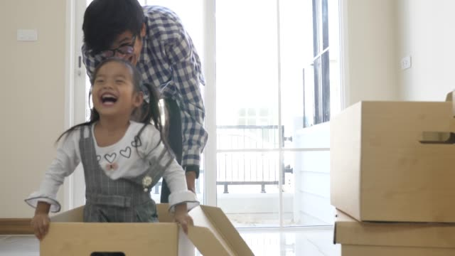daughter playing with her father in our new home, family so happy moment - genitori video stock e b–roll