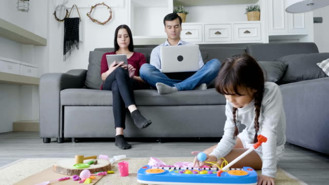 Daughter playing with toys on floor while father and mother working in background video