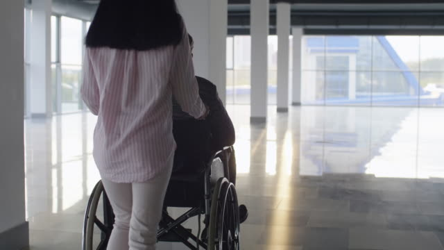 Daughter pushing father in wheelchair Tilt down shot of young woman pushing man in wheelchair through spacious hall pushing wheelchair stock videos & royalty-free footage