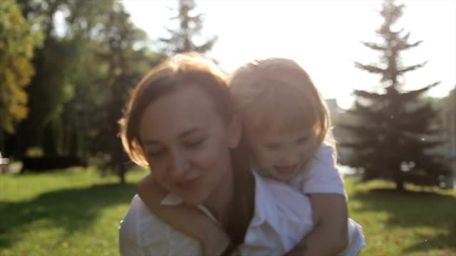 stockvideo's en b-roll-footage met dochter rijden bij moeder in een stadspark bij zonsondergang - garden house