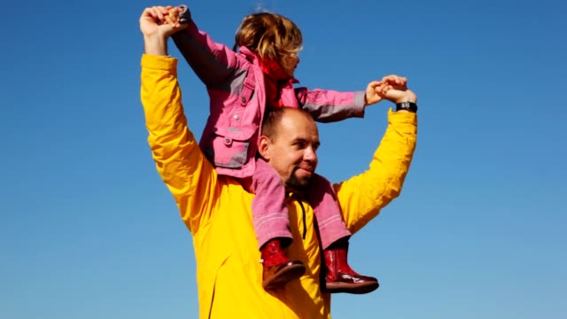 Daughter sits at daddy on shoulders against sky video
